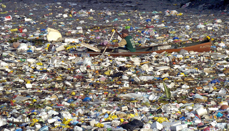 Man in small boat going thru litter from Pacific Garbage Patch