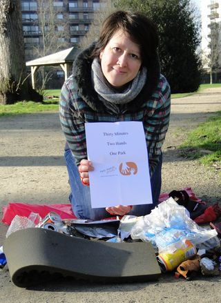 Eef, PPAL kneeling in front of litter with 2 Hands Project sign